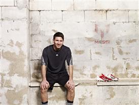 Leo Messi next to the new adizero f50 Messi boots