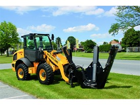 New Holland Construction with a tree removal implement attached