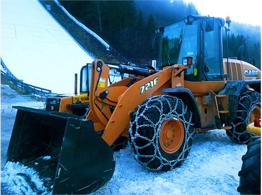 Case 721F wheel loader, equipped with snow chains, at work at the ski flying championships in Austria.