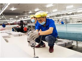 Yang Liu and Weisuo Xia cut fabrics that will be made into chair- and sofa covers for IKEA