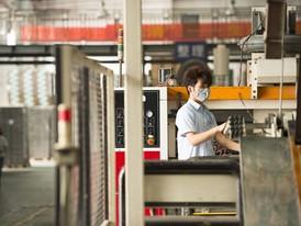 Zhong Bo operates the printing machine at Dongguan MYS