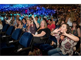 Attendees cheer the opening general session