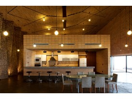 A view of the dining room and kitchen of a House (Las Anitas) in Paraguay designed by Cabral's architecture firm, Gabine