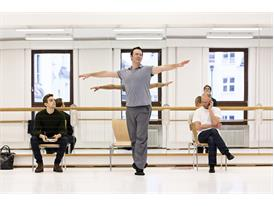 While protégé Myles Thatcher (seated left) observes, mentor Alexei Ratmansky performs a dance gesture for dancers of the