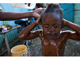 A Father Bathes his Son Outside their Home in La Grua, Dominican Republic