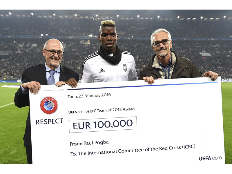 ICRC doctor Alberto Cairo receives a cheque for €100,000 from Paul Pogba, who presented on behalf of UEFA