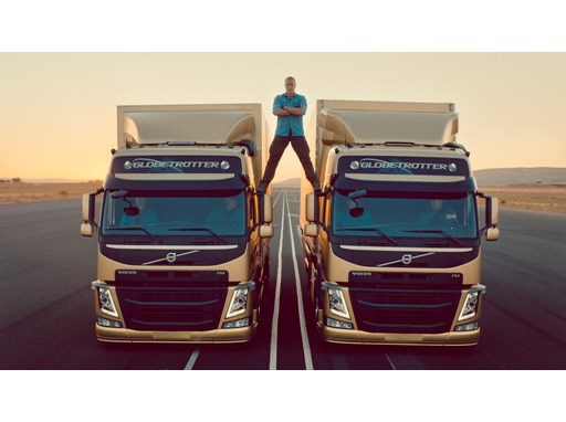 Jean-Claude Van Damme stands between two Volvo FMs as they drive in reverse, before attempting to do his trademark split