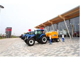 New Holland tractors and balers in front of the new industrial complex in Harbin