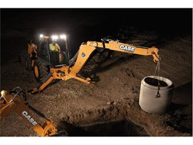 Backhoe winching a concrete pipe section into place at night