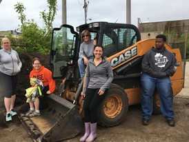 Victory Garden Initiative volunteers gather around CASE SV300 skid steer loader