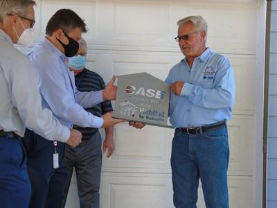 Bill Bauck Wichita Habitat for Humanity Board member presents a plaque to CASE
