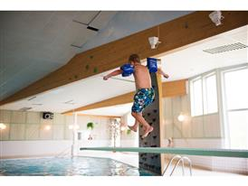 Johannes Hallindemo jumps into the swimming pool at Gyllensvaans Möbler