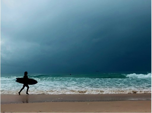 A surfer walking on the beach