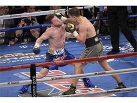 Gennady Golovkin (gray trunks) hits Canelo Alvarez with a right
