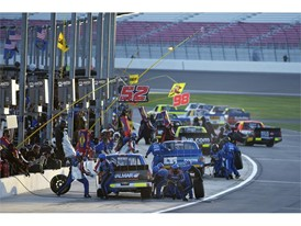 Pit crews swarm their trucks during the NASCAR Camping World Truck Series