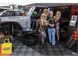 An attendee poses with booth models in the Fox Factory shock absorber equipment company booth