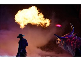 A bull rider introduced with a fire breathing bull statue