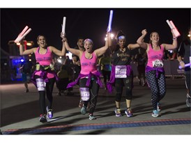 A group of women cross the finish line during the Rock 'n' Roll Las Vegas Marathon 5K run