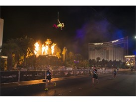 Runners pass under an aerialist as the Mirage volcano erupts during the Rock 'n' Roll Las Vegas Marathon