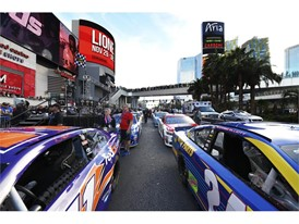 Stock cars are lined up outside Planet Hollywood and the Miracle Mile Shops during the NASCAR Victory Lap