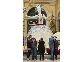 Visitors pause for a photo with the 18-foot tall Ice Princess towering over the Bellagio Conservatory and Botanical Gard