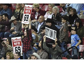 Supporters of bull rider Tim Bingham cheer him on
