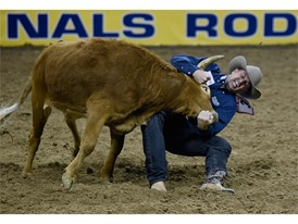 Olin Hannum from Malad, Idaho, competes in steer wrestling during the seventh go-round of the National Finals Rodeo
