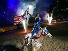 A rider carries the American flag during the opening ceremonies at the start of the seventh go-round of the NFR