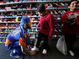 Boise State Broncos linebacker Breydon Boyd helps Daniel Mejia with the fit of a shoe