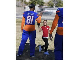 Genisses Jimenez hands a football back to Boise State's Akilian Butler