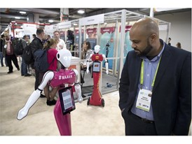 Edwin Martinez checks out a robot from French start-up Event Bots during the first day of CES