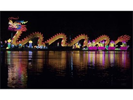A large dragon is reflected in a pond on the opening night of the China Lights lantern festival