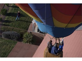 A resident watches as a balloon floats overhead during the Mesquite Hot Air Balloon Festival