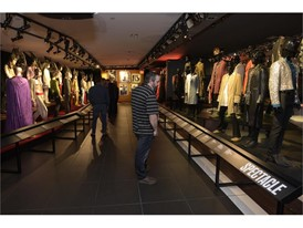 """Guests look at a collection of stage outfits at the Rolling Stones """"Exhibitionism"""""""