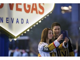 ans take a photo in front of a replica of the Welcome to Fabulous Las Vegas sign
