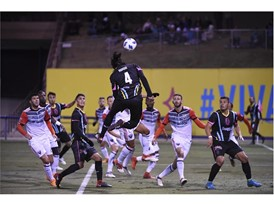 Players watch as Las Vegas Lights Joel Huiqui heads the ball towards the goal