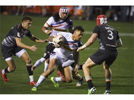 Maka Unufe of the US makes his way through England's defense during their match at the USA Sevens Rugby tournnament