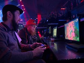Jonathan Bart, left, and Chandler Ewing play a console game during the grand opening of Esports Arena