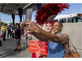 Las Vegas showgirl  Porsha Revesz, left, poses for a photo with a passenger at the Bonneville RTC Transit Station
