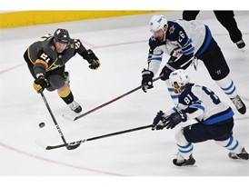 Vegas Golden Knights center Cody Eakin (21) tries to swat the puck away from Winnipeg Jets