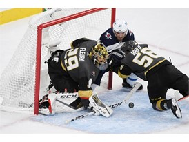 Vegas Golden Knights left wing Erik Haula shoves Winnipeg Jets center Mark Scheifele into the net