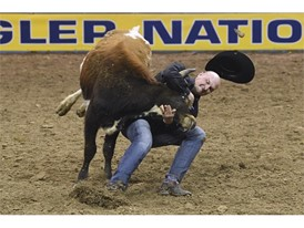 Kyle Irwin competes in steer wrestling