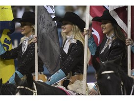 Cowgirls carry sponsor flags