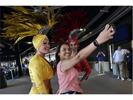 A fan takes a selfie with Las Vegas showgirls