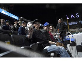 A fan holds up a foul ball
