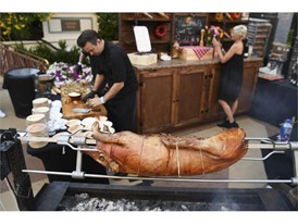 A pig roasts on a spit at the Buddy V's booth