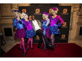 Performers dressed as Effie Trinket walk the red carpet