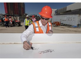 LVCVA CEO/President Steve Hill signs his name to the final beam