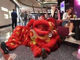 A woman watches as performers from the Lohan School of Shaolin take a break from a lion dance