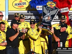 Joey Logano (22) is presented with a trophy after winning the NASCAR Cup Series Pennzoil 400